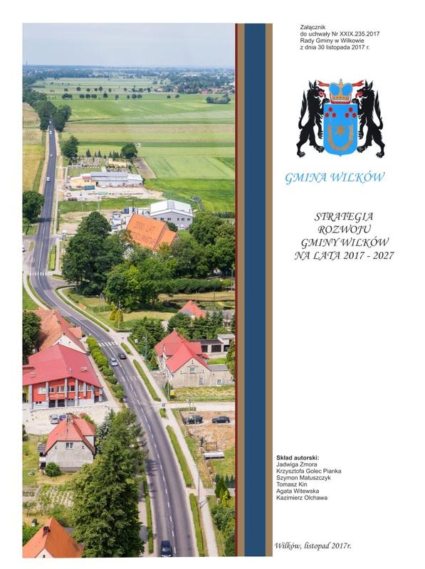 Widok na drogę nr 451 przecinającą wieś Wilków. Strona tytułowa dokumentu pt. Strategia rozwoju Gminy Wilków na lata 2017 - 2027.