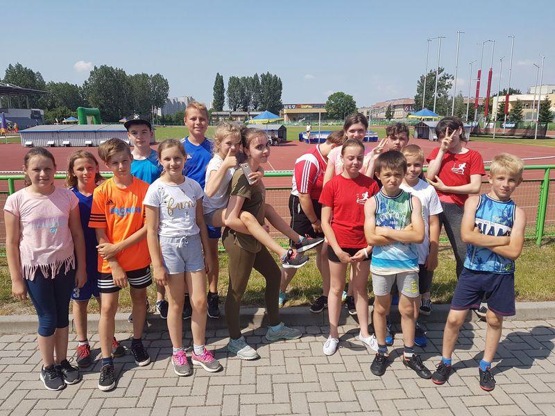 Na pierwszym planie grupa dzieci i młodzieży w strojach sportowych. Za nimi bieżnia stadionu.