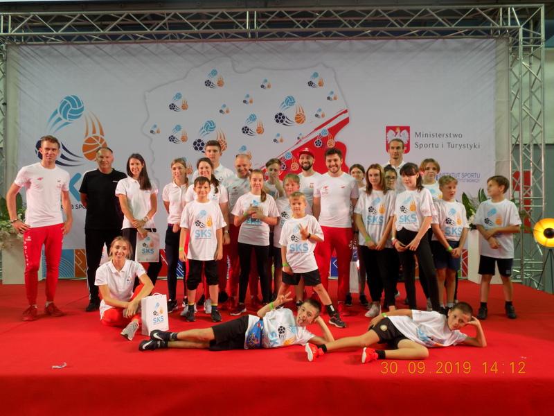 Zdjęcie grupy dzieci wraz z opiekunem i sportowcami na tle czerwonego dywanu przykrywającego podium oraz baneru promującego wydarzenie.