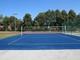 Zdjęcie przedstawia widok niebieskiej planszy boiska do gry w piłkę siatkową, za boiskiem widoczne drzewa.
