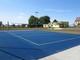 Na pierwszym planie widok niebieskiej planszy boiska do gry w piłkę siatkową, drugi plan przedstawia otaczające boisko budynki.